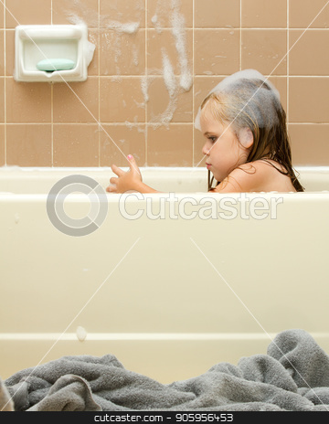 Young child cleaning in the tub stock photo, Image shows young girl covered in soap suds getting clean while taking a bath. by txking