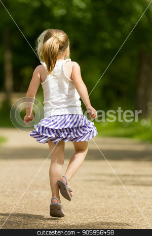 Young girl skipping away stock photo, Young female child skipping on a rock path in the spring time. Back is facing the camera as she is skipping away. by txking