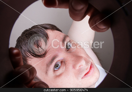 What is in there stock photo, Man looking through a hole and trying to reach through or at least take a peek by txking