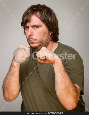 Fist up and ready to brawl stock photo, A guy ready to fight with his fist up in the air by txking
