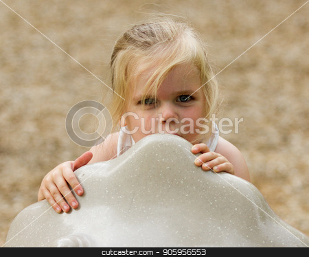 Child hiding behind a object at the playground stock photo, Playing a game of hide and seek. With her expression though can be used for other uses. by txking