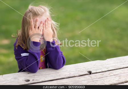 Game of hide and seek stock photo, Preschooler playing game of hide and sick. Right now she is sitting on the table covering her eyes while taking a sneaky peek. by txking