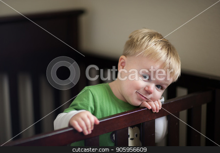 Waiting in his crib for his time to get out stock photo, Toddler is in his crib smiling while wanting to get out. by txking