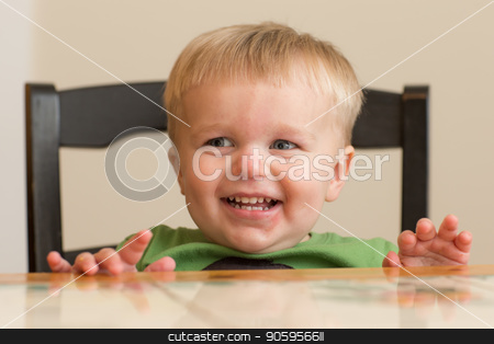 Young man wants food stock photo, Little guy is sitting at the table waiting for his food to come. Has a big smile on his face. by txking