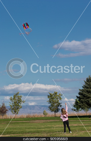 Young girl flying a kite stock photo, Kite way up high in the sky at the park for this young girl by txking
