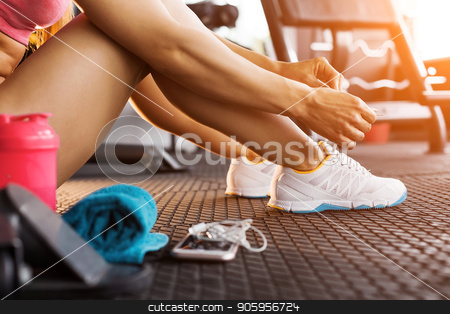 woman tying trainers in the gym close up stock photo, close up photo of woman tying shoelaces of white trainers siting on a mat surrounded by smart phone, earphones, towel and a shaker in the sun lightened gym by Oleh