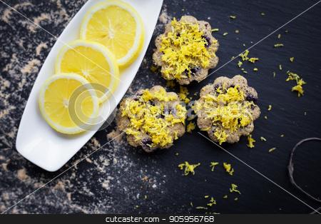 lemon cupcakes on a black background stock photo, lemon cupcakes on a black background and a lemon on a plate by Sergiy Artsaba