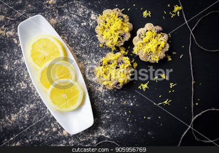 lemon cupcakes on a black background stock photo, lemon cupcakes on a black background and a lemon on a plate by Sergiy Artsaba