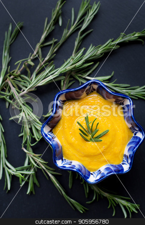 pumpkin soup on a black background with the sprigs of rosemary, close-up stock photo, pumpkin soup on a black background with the sprigs of rosemary, close-up. by Sergiy Artsaba