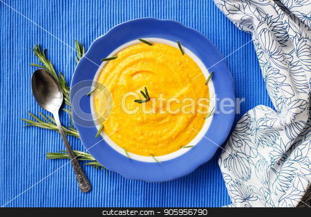 pumpkin cream soup in a blue plate on blue napkin, a branch of rosemary stock photo, pumpkin cream soup in a blue plate on blue napkin, a branch of rosemary. by Sergiy Artsaba