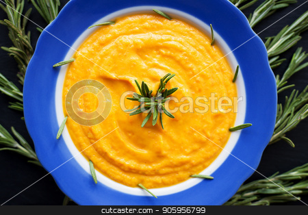 pumpkin soup with rosemary branches on a black background with a blue napkin stock photo, pumpkin soup with rosemary branches on a black background with a blue napkin. by Sergiy Artsaba