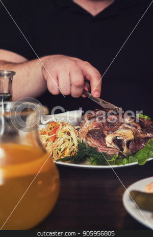 Man eats tasty dish of pork shank stock photo, Man eats tasty dish of pork shank, closeup photo by olinchuk