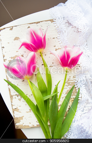 Three beautiful pink tulips on old white table stock photo, Three beautiful pink tulips on old white table. by Sergiy Artsaba