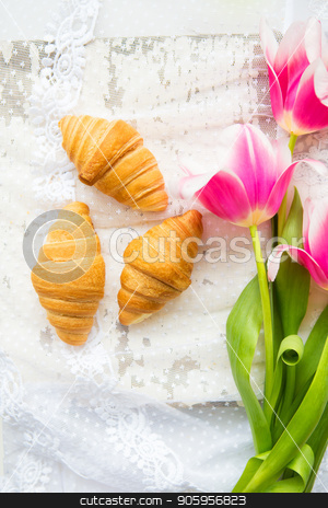 Three croissants and bright pink tulips on lace tablecloth, close-up stock photo, Three croissants and bright pink tulips on lace tablecloth, close-up. by Sergiy Artsaba