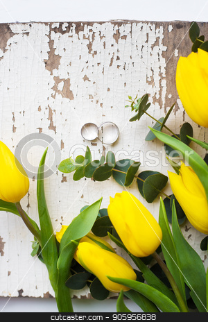 wedding rings with yellow tulips on old white table stock photo, wedding rings with yellow tulips on old white table by Sergiy Artsaba