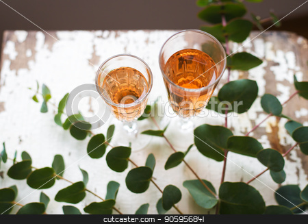 eucalyptus branches on an old table with a glass of rose wine stock photo, eucalyptus branches on an old table with a glass of rose wine by Sergiy Artsaba