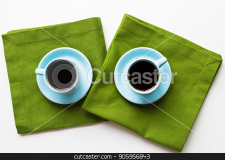 freshly brewed coffee stock photo, two blue cups of coffee on a table with green cloth by Sergiy Artsaba
