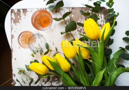 yellow tulips on a white table with glasses of rose wine stock photo, yellow tulips on a white table with glasses of rose wine by Sergiy Artsaba