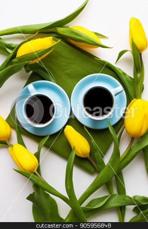 freshly brewed coffee stock photo, two blue cups of coffee on a table with green cloth and yellow tulips by Sergiy Artsaba