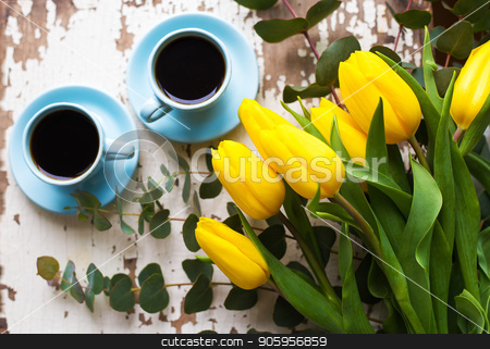 freshly brewed coffee stock photo, two blue cup of coffee with yellow tulips on an old table by Sergiy Artsaba