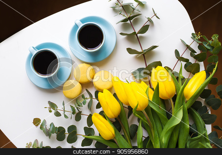 freshly brewed coffee stock photo, two blue cup of coffee with yellow tulips on an old table, top view by Sergiy Artsaba
