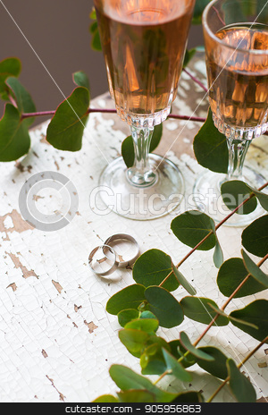glass of rose wine stock photo, Eucalyptus branches on an old table with a glass of rose wine and wedding rings, close-up by Sergiy Artsaba