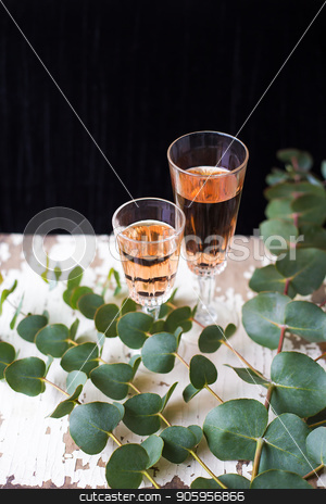 glass of rose wine stock photo, eucalyptus branches on an old table with a glass of rose wine by Sergiy Artsaba