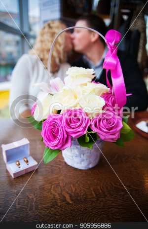 bouquet of flowers and wedding rings in a box on a background kissing couple stock photo, bouquet of flowers and wedding rings in a box on a background kissing couple. by Sergiy Artsaba