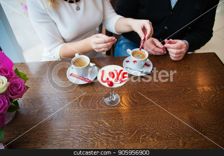 dessert with words of love and a cherry on a background of couples with coffee stock photo, dessert with words of love and a cherry on a background of couples with coffee. by Sergiy Artsaba