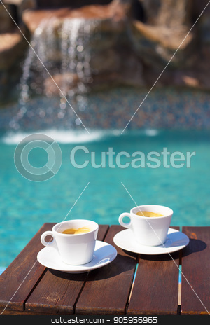 Two cups of coffee on the table near the pool stock photo, Two cups of coffee on the table near the pool. by Sergiy Artsaba