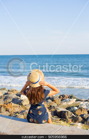 Beautiful girl in a hat sits near the sea on stones stock photo, Beautiful girl in a hat sits near the sea on stones. by Sergiy Artsaba
