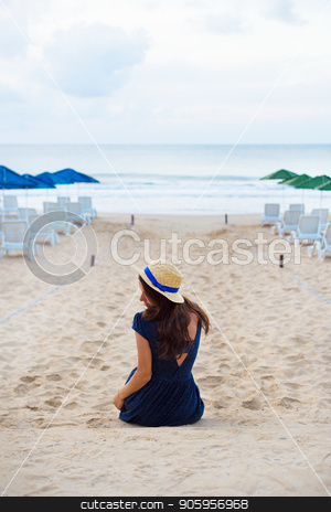 Beautiful girl in a hat sits with her back on a sandy beach stock photo, Beautiful girl in a hat sits with her back on a sandy beach. by Sergiy Artsaba