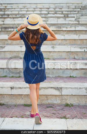 Beautiful girl on the steps in a blue dress and hat stock photo, Beautiful girl on the steps in a blue dress and hat. by Sergiy Artsaba