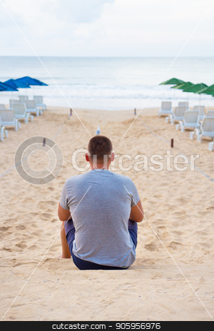 Young guy sits with his back on a sandy beach stock photo, Young guy sits with his back on a sandy beach. by Sergiy Artsaba
