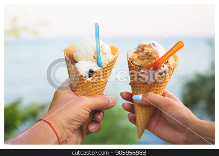 Beautiful bright ice cream with different flavors in the hands of a couple stock photo, Beautiful bright ice cream with different flavors in the hands of a couple. by Sergiy Artsaba