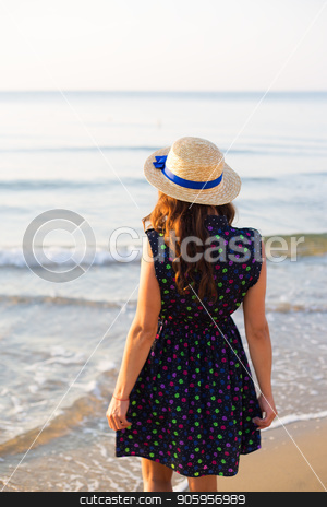 Beautiful girl in a hat stands with her back on a sandy beach. stock photo, Beautiful girl in a hat stands with her back on a sandy beach by Sergiy Artsaba