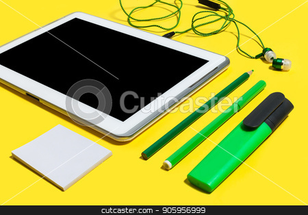 set of office stationary and gadgets stock photo, set of business or education accessories. green pencils, headphones, paper stickers, markers and tablet pc lying on a yellow background. concept of the office gadgets and stationary by Oleh