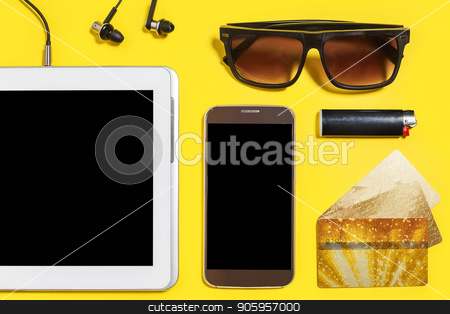 collection of modern people attributes on a yellow background stock photo, tablet pc, smartphone earphones, cigarette lighter, sock, sunglasses and a gold bank cards lying on a yellow surface. concept of modern people accessories. top view by Oleh