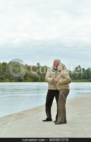 Happy senior couple near water stock photo, Happy senior couple near water at autumn park by Ruslan Huzau