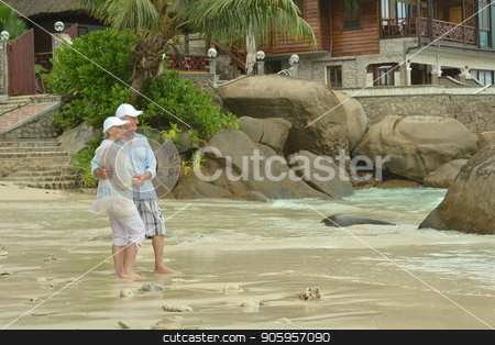 Happy elderly couple hugging stock photo, Happy elderly couple hugging  on tropical  beach by Ruslan Huzau