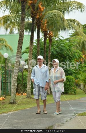 Senior couple at  hotel resort stock photo, Senior beautiful couple walking at tropic resort by Ruslan Huzau