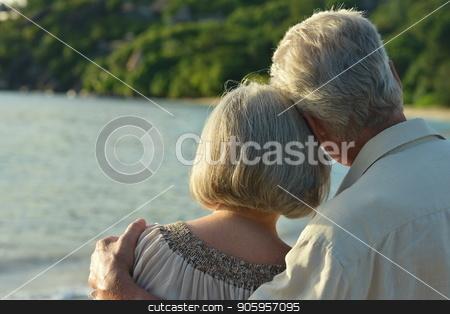 Happy elderly couple hugging stock photo, Happy elderly couple hugging  on tropical  beach by Ruslan Huzau