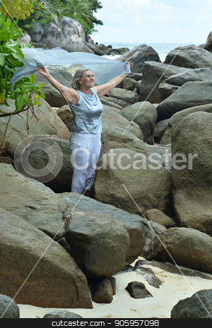 Portrait of mature woman stock photo, Portrait of mature woman standing at sandy beach with rocks by Ruslan Huzau