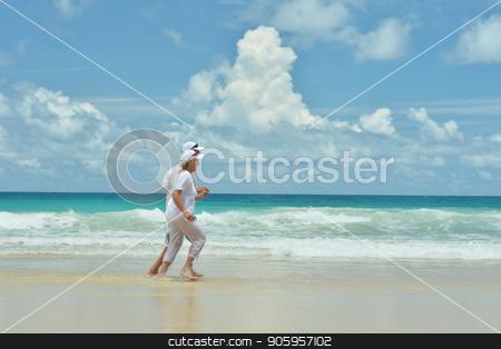 Happy elderly couple running stock photo, Happy elderly couple running  on tropical  beach by Ruslan Huzau