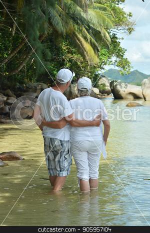 Happy elderly couple resting stock photo, Happy elderly couple resting on  beach embracing by Ruslan Huzau