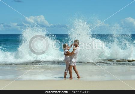 Happy elderly couple dancing stock photo, Happy elderly couple dancing  on tropical  beach by Ruslan Huzau