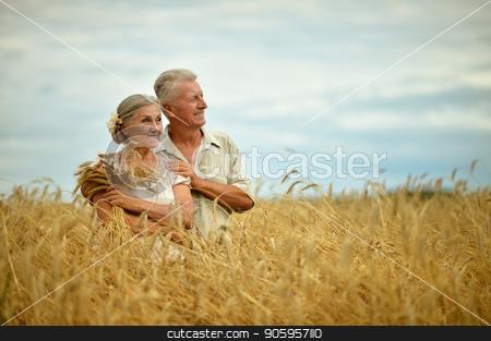 Senior couple resting at  summer field stock photo, Senior couple hugging at summer field  during vacation by Ruslan Huzau