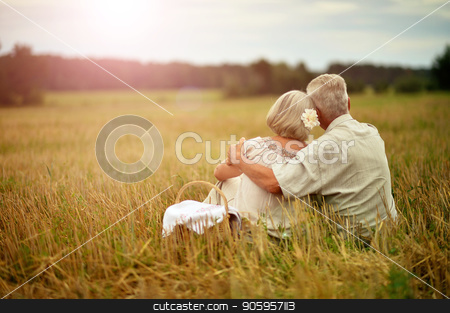 Senior couple resting at  summer field stock photo, Senior couple sitting at summer field  during vacation by Ruslan Huzau