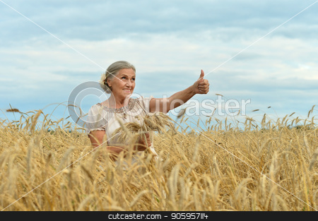 senior woman in summer field stock photo, Portrait of a senior woman showing thumb up in summer wheat field by Ruslan Huzau
