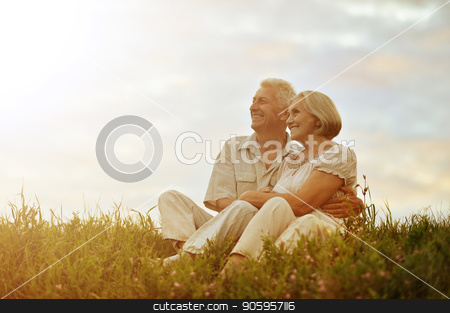Senior couple resting at summer field stock photo, Senior couple sitting at green summer field during vacation by Ruslan Huzau